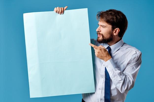 Presentazione del foglio blu dell'uomo bello che fa pubblicità allo sfondo blu
