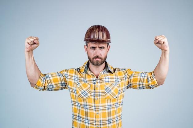 Un bell'uomo costruttore in casco di sicurezza da costruzione e camicia a scacchi dimostra potenza sul cantiere, forza maschile.