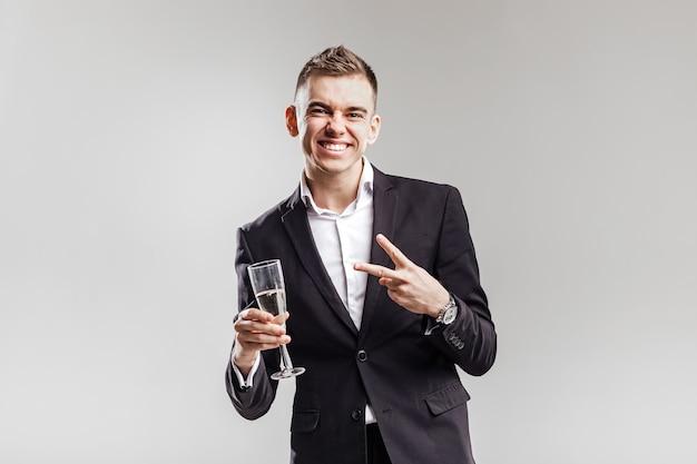 Un bell'uomo in giacca e cravatta sorride e tiene un bicchiere di champagne su uno sfondo bianco. tempo di festa .