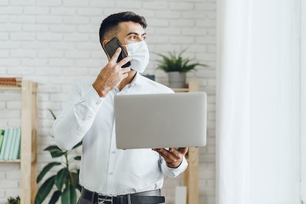 Uomo d'affari bello dell'uomo nella mascherina medica usando il suo computer portatile mentre parla sul suo cellulare all'interno