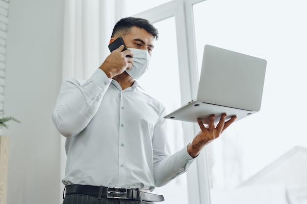 Uomo d'affari bello dell'uomo nella mascherina medica usando il suo computer portatile mentre parla sul suo cellulare