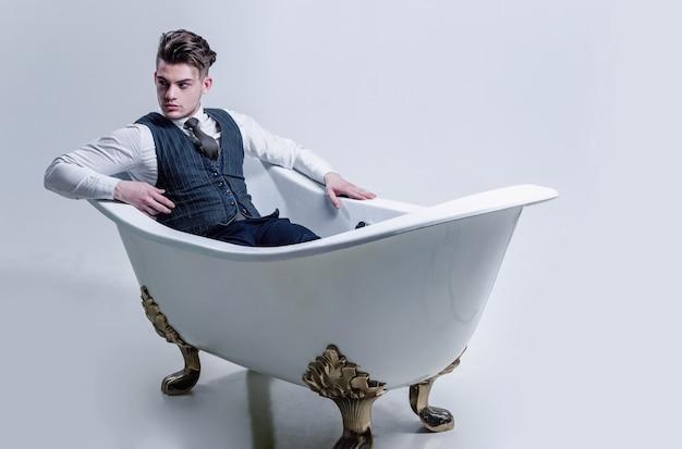 Bell'uomo o uomo d'affari con taglio di capelli alla moda, capelli, abbigliamento da lavoro di moda, gilet, cravatta, camicia e pantaloni che si rilassano nel bagno classico, vasca bianca, su sfondo grigio