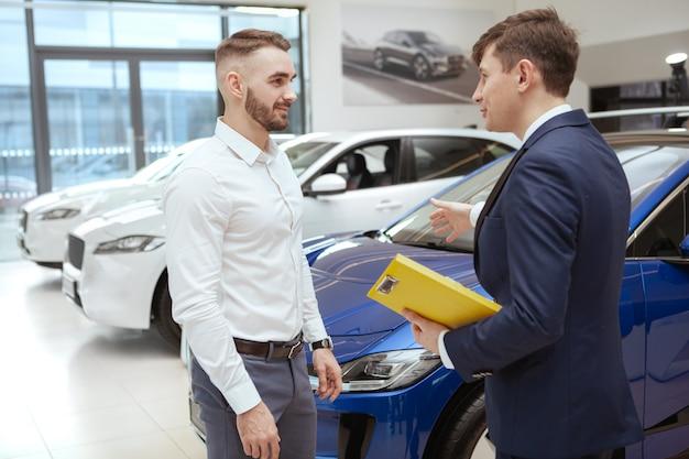Uomo bello che compra nuova automobile al concessionario