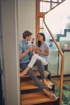 Un bell'uomo e una donna allegra seduti sulle scale di legno mentre si divertono nella lussuosa casa moderna