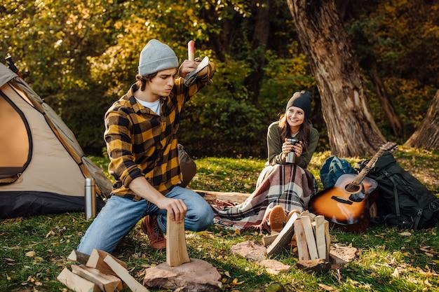 Bell'uomo che taglia legna con l'ascia. la donna attraente beve il tè e si siede sul ceppo