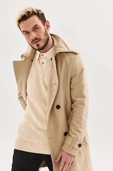 Uomo bello nel look attraente di moda studio cappotto