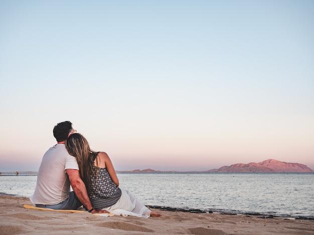 Uomo bello e carino donna seduta sulla spiaggia