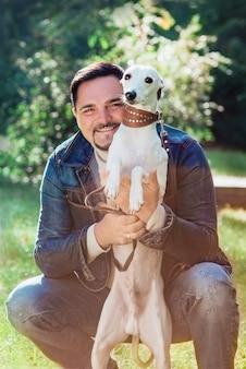 Bell'uomo in abiti di jeans con cani whippet all'aperto