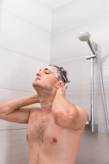 Un bell'uomo che lava diligentemente i capelli gocciolanti di schiuma nella cabina doccia nel moderno bagno piastrellato