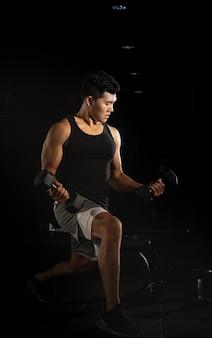 Uomo bello che fa esercizio per buit muscolo, corpo in forma e soda