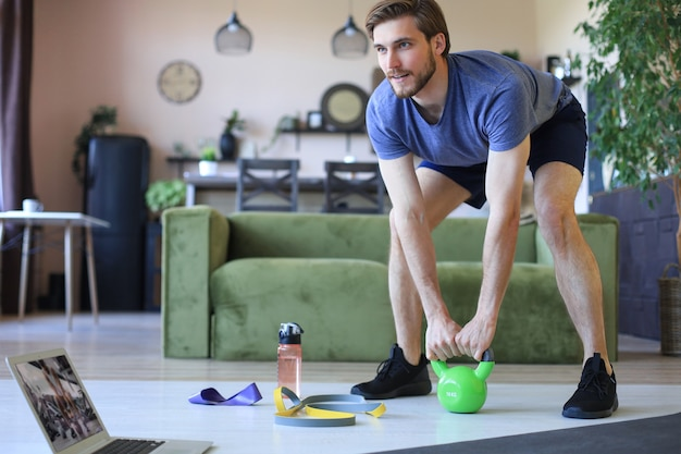 Bell'uomo che fa esercizio sportivo a casa durante la quarantena. concetto di vita sana.