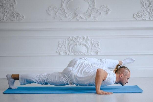 Uomo bello che fa posa di yoga isolata
