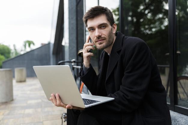 Bell'uomo vestito con un cappotto seduto per strada, utilizzando il computer portatile, parlando al telefono cellulare