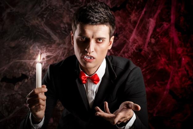 Bell'uomo vestito con un costume da dracula per halloween. il vampiro attraente con le candele allunga la mano in avanti