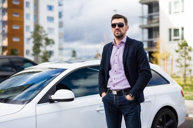 Autista uomo bello in occhiali da sole in posa vicino alla sua auto