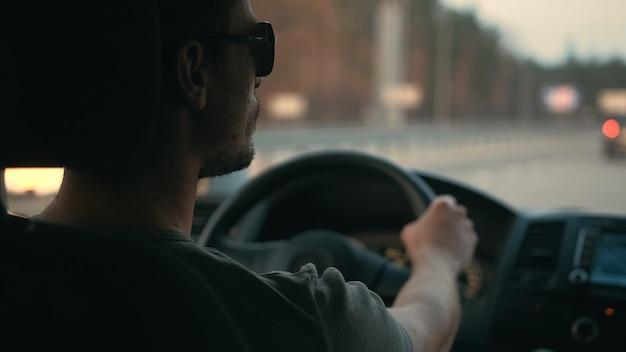 Il bell'uomo guida la macchina lungo l'autostrada