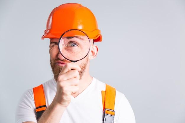 Ingegnere uomo bello nella costruzione di un casco protettivo sul muro grigio, giocoso e positivo con lente d'ingrandimento