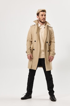 Acconciatura alla moda da uomo bello per lo stile del cappotto autunnale che guarda allo sfondo chiaro laterale