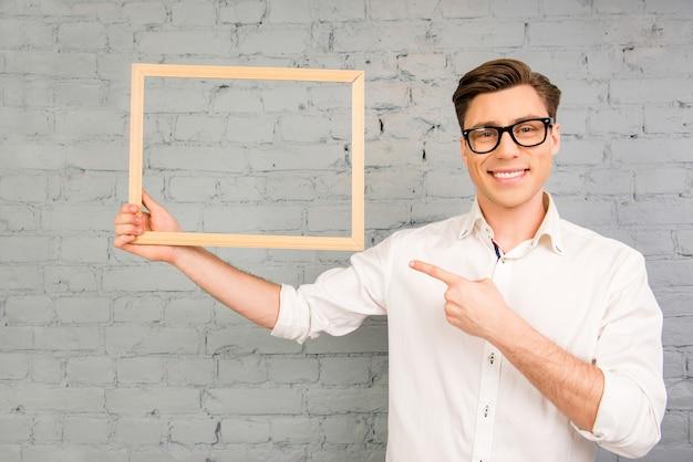 Uomo bello con gli occhiali che punta sul telaio in legno in mano