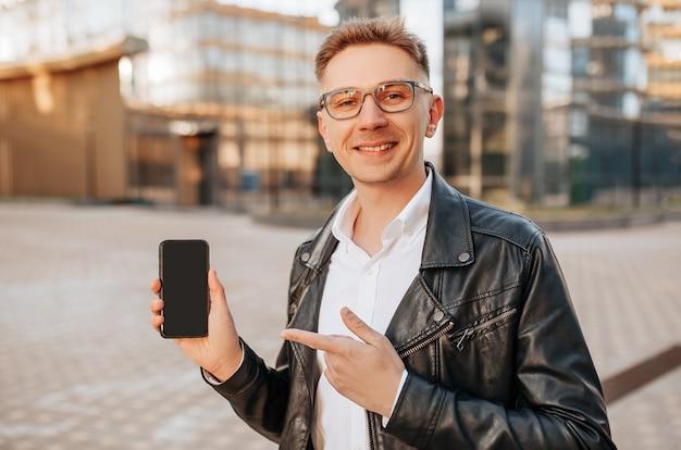 Bell'uomo con gli occhiali con uno smartphone sulla strada di una grande città. l'uomo d'affari punta il dito sullo schermo del telefono sullo sfondo urbano