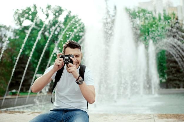 Uomo bello divertendosi in città con la macchina fotografica davanti alla fontana incredibile