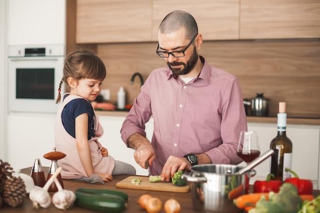 Bell'uomo e la sua graziosa piccola figlia stanno cucinando insieme lo stufato di verdure in cucina. concetto di cibo sano e vegetariano.
