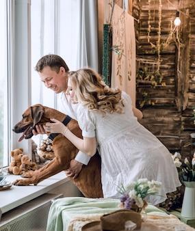 Bell'uomo e il suo cane guardando attraverso la finestra nel suo appartamento. il concetto di attesa