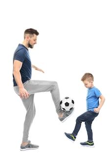 Uomo bello e suo figlio che giocano a calcio isolato Foto Premium
