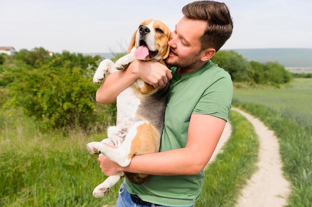 Uomo bello che tiene cane da lepre sveglio nel parco