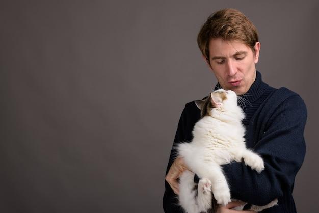 Uomo bello che tiene simpatico gatto contro il muro grigio
