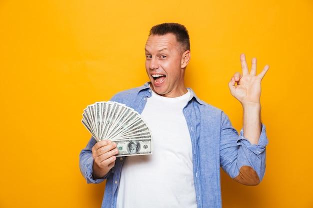 Uomo bello che tiene soldi che mostrano gesto giusto.