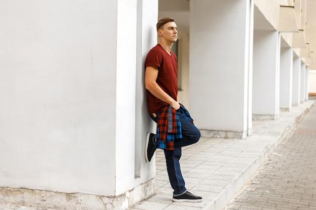 Uomo bello che tiene una camicia e posa vicino a un muro bianco
