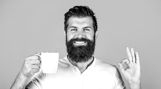 L'uomo bello tiene una tazza di caffè, tè. uomo barbuto che sorride mostrando segno ok. buongiorno, uomo tè, ok. uomo sorridente dei pantaloni a vita bassa con la tazza di caffè fresco, uomo felice che mostra il segno giusto. concetto di mattina