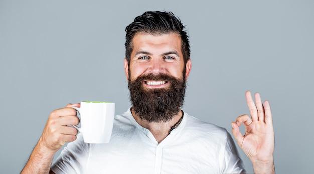 L'uomo bello tiene la tazza di tè del caffè