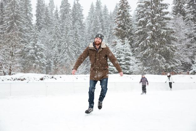 Uomo bello che pattina sul ghiaccio all'aperto con la neve