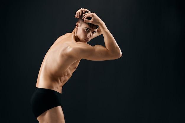 Uomo bello gonfiato corpo nudo in mutandine scure in posa muro isolato