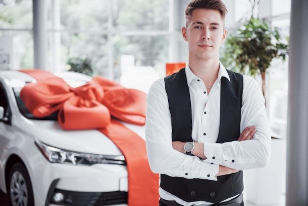 Un bell'uomo è un acquirente in piedi accanto a una macchina nuova al centro del concessionario e guarda la telecamera.