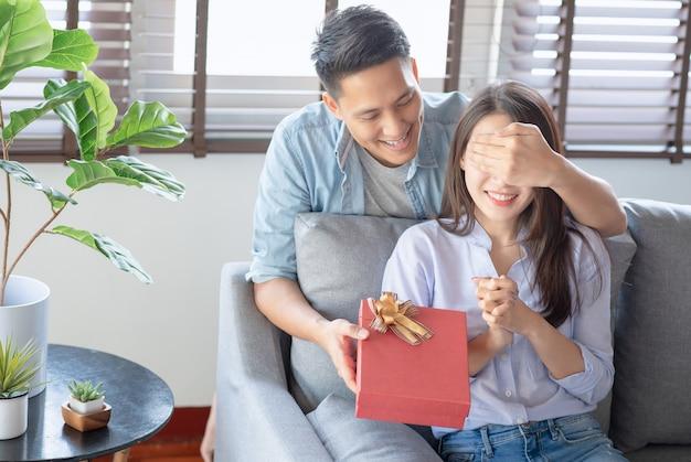 Bell'uomo sta dando alla sua ragazza una confezione regalo rossa per il compleanno sorprendente nel soggiorno di casa