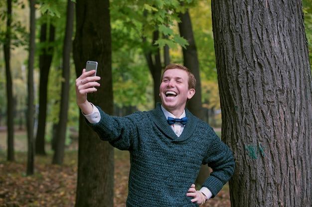 L'uomo bello sta prendendo un selfie all'aperto - gente caucasica - concetto della natura, della gente, di stile di vita e della tecnologia