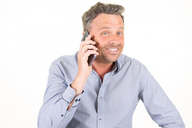 Uomo bello sopra fondo bianco isolato che mantiene il telefono cellulare reale di conversazione