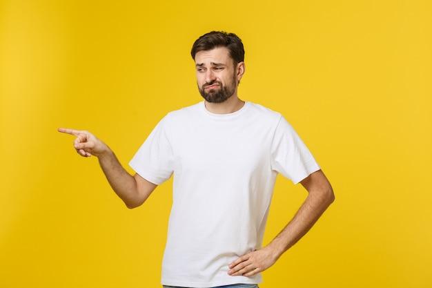 Uomo bello sopra la parete gialla isolata frustrata e indicante la parte anteriore