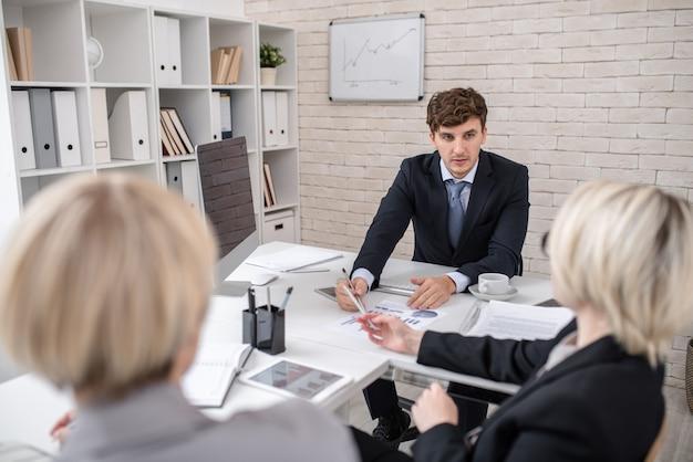 Uomo bello che conduce riunione d'affari importante in ufficio
