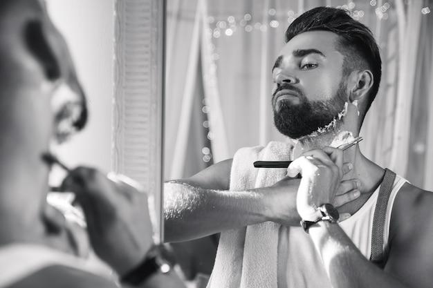 Bell'uomo guardarsi allo specchio e radersi la barba con un rasoio a mano libera