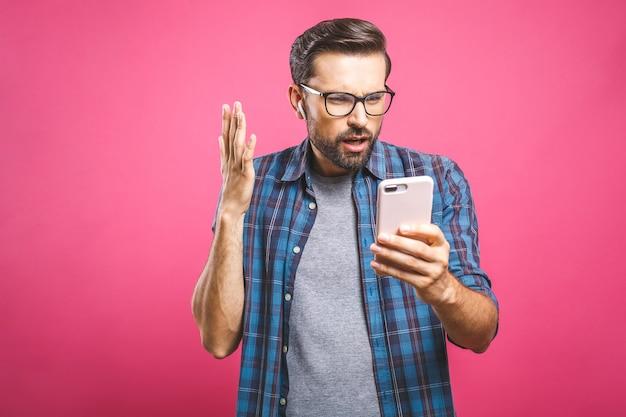 L'uomo bello sembra colpito in smartphone. concetto di persone, emozioni e tecnologia.