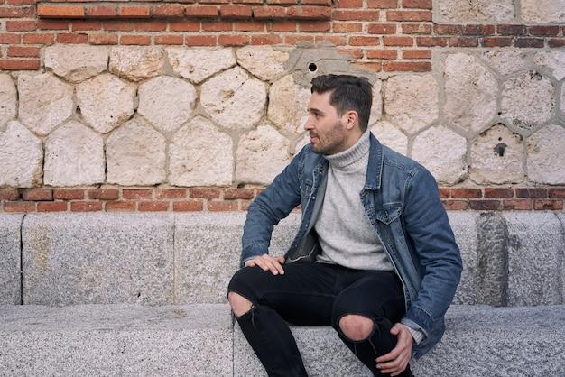 Bell'uomo guarda lateralmente con un muro di mattoni