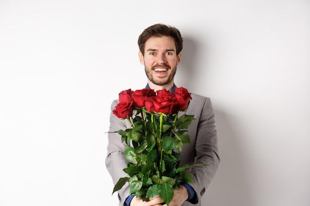 Bell'uomo innamorato che augura felice giorno di san valentino, dando bouquet di fiori su appuntamento romantico, sorridendo alla telecamera, indossando tuta su sfondo bianco.
