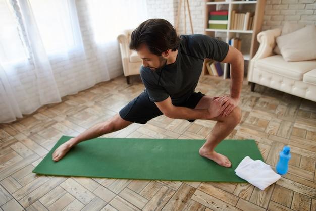 L'uomo bello fa gli esercizi di allungamento per la gamba.