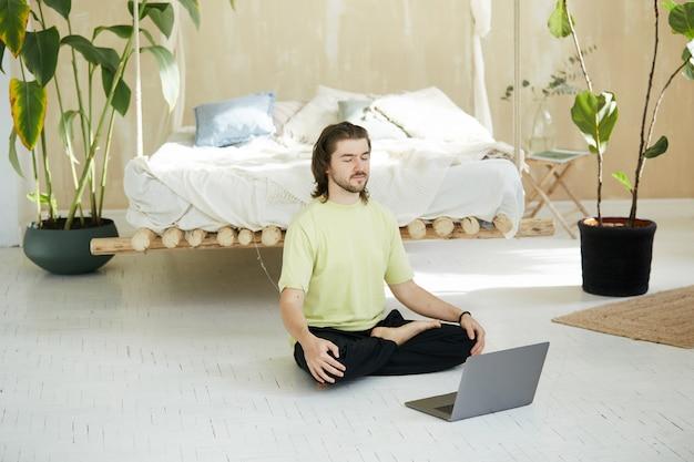 Bell'uomo che medita con il laptop sul lato, concentrazione e pratica respiratoria a casa online attraverso lezioni web, yoga e meditazione
