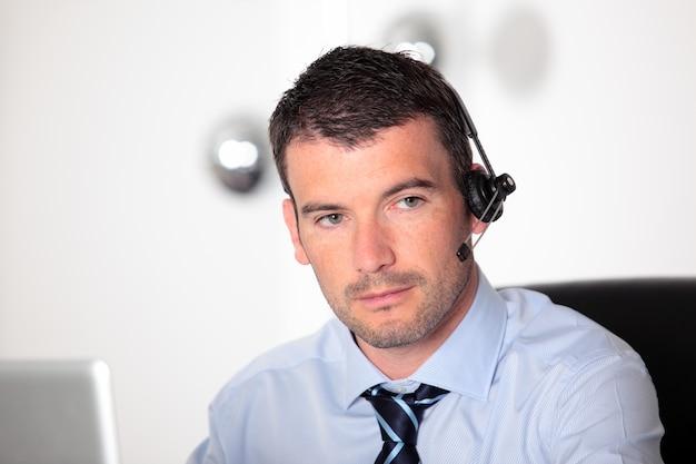 Bell'uomo in ufficio con auricolare e computer
