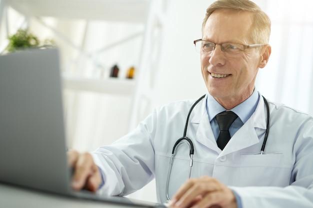 Un bell'uomo medico che lavora al computer portatile e sorride mentre è seduto al tavolo nel suo ufficio in clinica